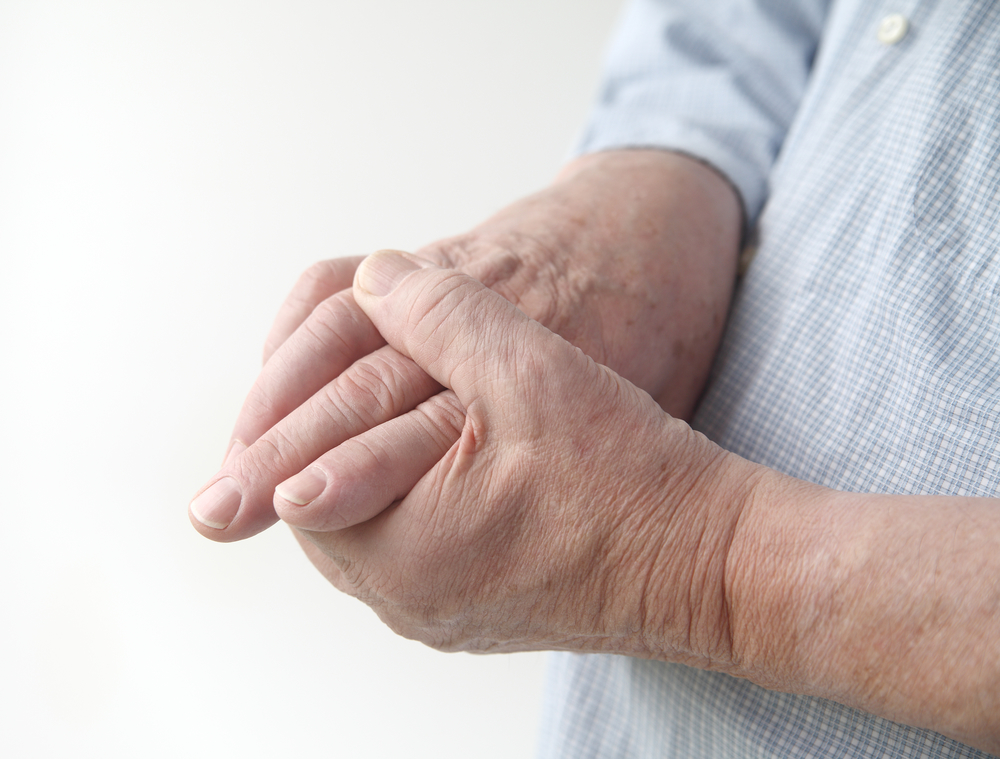 man rubs hands for arthritis pain