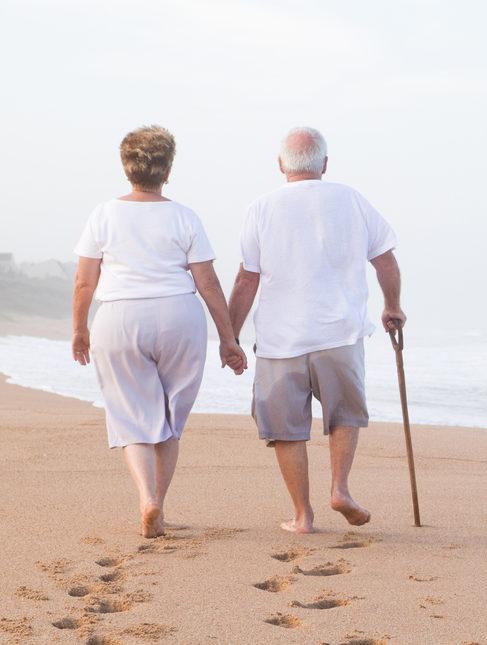 elderly couple man with cane on beach