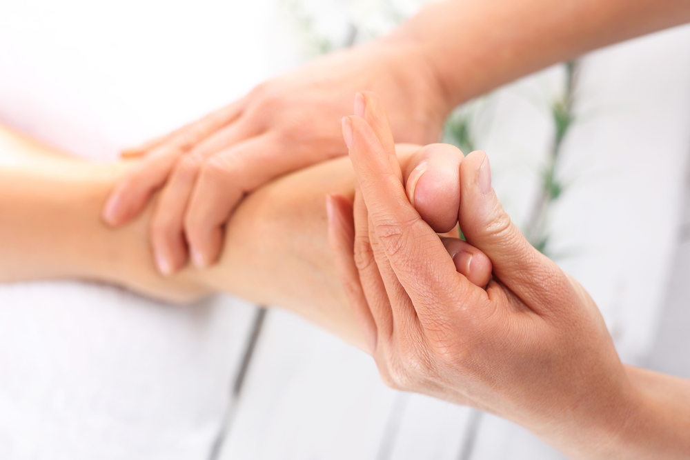 massaging foot with neuropathy
