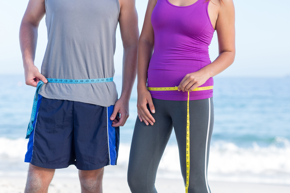 couple losing weight measuring waists