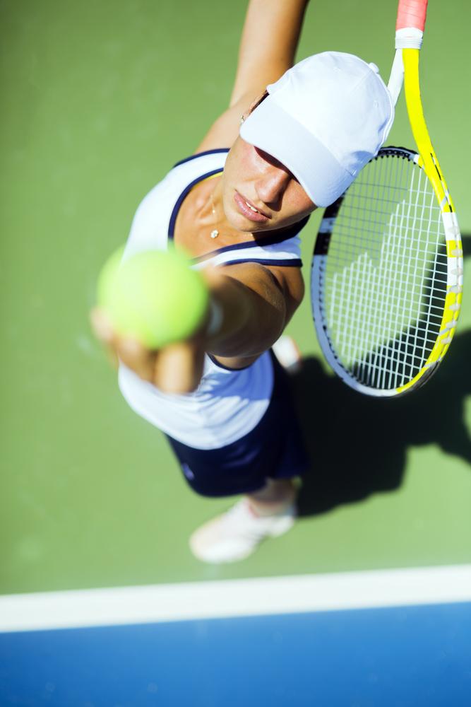 woman serving tennis ball pain free