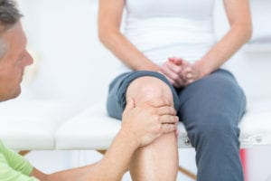 Male doctor assessing knee pain