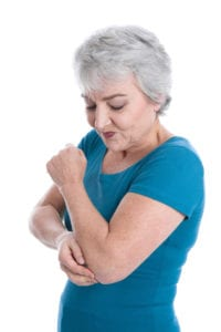 older woman has joint pain in elbow