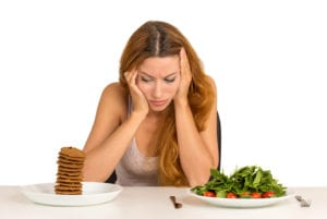 young woman deciding between healthy and unhealthy foods