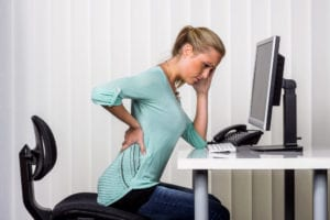 woman sitting at desk with back injury