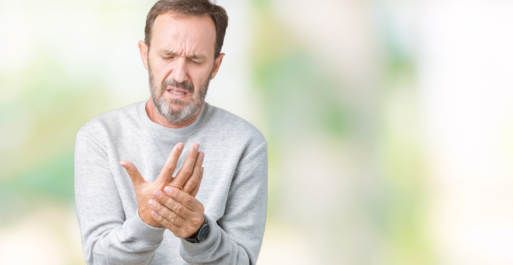 Handsome middle age man suffering pain on hands and fingers, arthritis inflammation