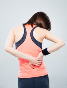 woman in exercise clothes experiencing back pain against solid gray backdrop